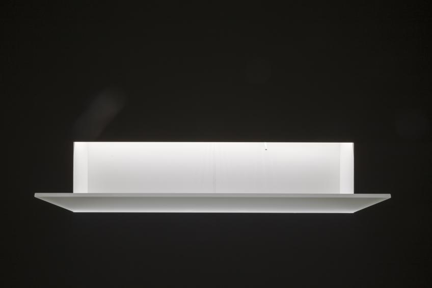 Corian sink that is inserted into the wall cavity and is visible only by a sheet of glass that protrudes from the surface.