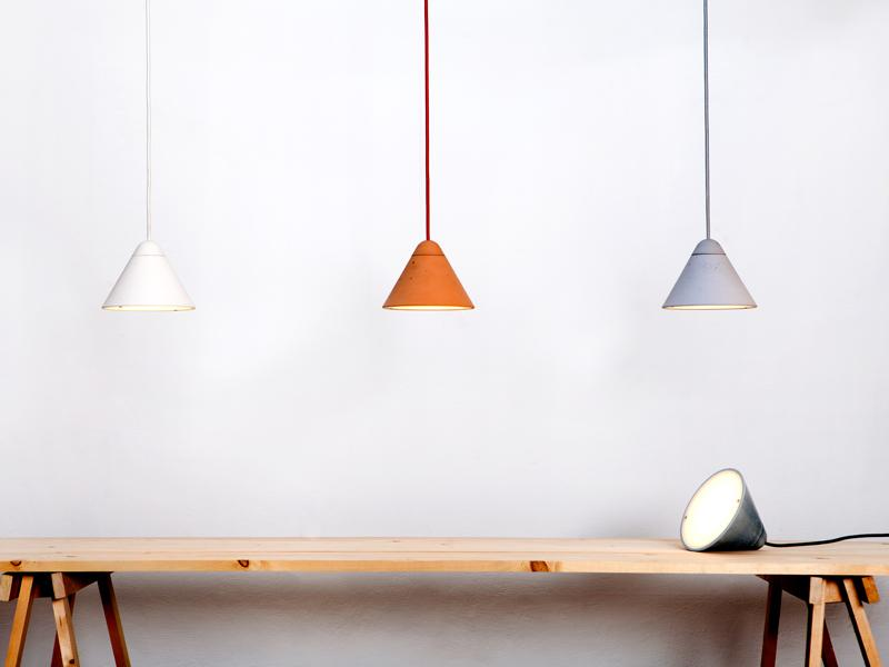 Three of Studio Itai Bar-On's Bullet lighting Collection, a line of hand-cast concrete lighting that is available in different sizes, tones, and finishes.